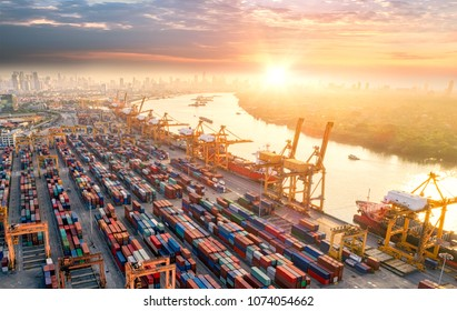 Aerial view from drone, Logistics and transportation of Container Cargo ship and Cargo plane with working crane bridge in shipyard at sunrise, logistic import export and transport industry background