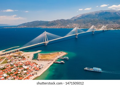 Aerial view from a drone on a beautiful large bridge for a highway across the sea in Patras, Greece. Refined, beautiful design of the bridge. Blue sea and sky. Part of the coast with buildings