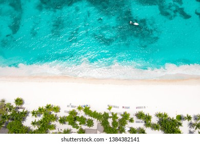 Aerial view from drone on caribbean island with coconut palm trees, sunbeds and boats floating in the sea. Summer vacations. Travel destination