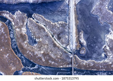 Aerial view from a drone on a frozen rural landcape. Ice frozen lake and river with a railroad bridge.