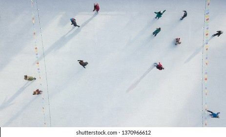 Aerial view of a drone on an open ice rink with people on a winter sunny day.