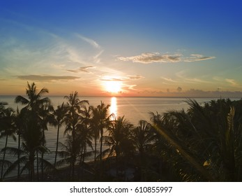 Aerial view from drone on palm trees and the sea on a sunset. Bali. Indonesia