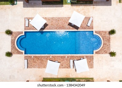 Aerial view from drone on poolside with swimming pool, umbrellas and sunbeds. Nobody. Summer holidays