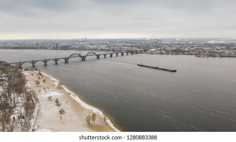 Aerial view from drone on railway bridge above Monastic island and Dnieper river in Dnipro city. Winter landscape and cityscape background. (Dnepr, Dnepropetrovsk, Dnipropetrovsk)