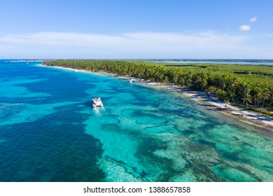 Aerial view from drone on tropical beach with palm trees and speed boats floating in caribbean sea
