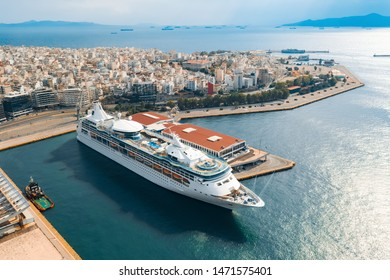 Aerial view from a drone of a panorama of a large multi-story cruise ship standing on a pier in the port of Piraeus, Greece. The ship cruises to the many islands of Greece, in the summer on sunny day