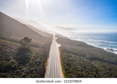 Aerial View Drone Shot of Highway Pacific Coast Highway California USA Big Sur Mountains Ocean Fog Sun