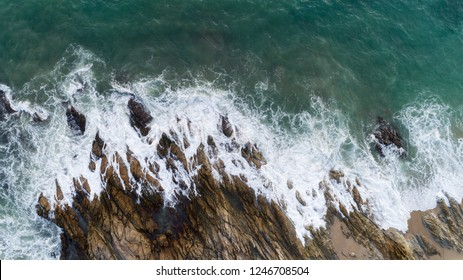 Aerial view drone shot of seascape scenic off beach in phuket thailand with wave crashing on the rocks