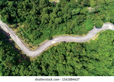 Aerial view drone shot top view of Asphalt road curve on mountain tropical rainforest with mountain peaks.