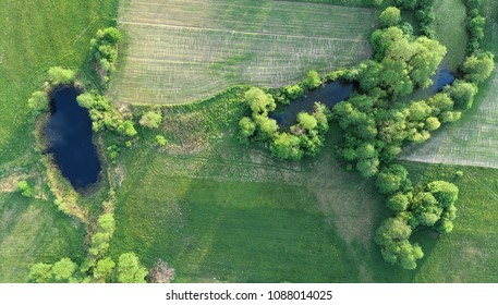 Aerial view from drone- small ponds between spring meadow