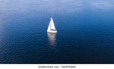 Aerial view from the drone of the yacht with white sails at sea.