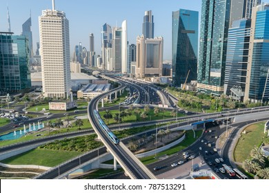 aerial view of a Dubai cityscape featuring roadway and train interchanges