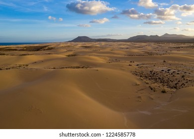 Aerial view of dunes at sunset with mountain range and beautiful skies in the background