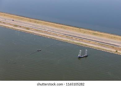 Aerial view Dutch afsluitdijk, separation between the fresh water lake IJsselmeer and the salt Wadden Sea