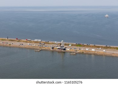 Aerial view Dutch afsluitdijk with watchtower and monument ir. Lely. The dam is the separation between the fresh water lake IJsselmeer and the salt Wadden Sea
