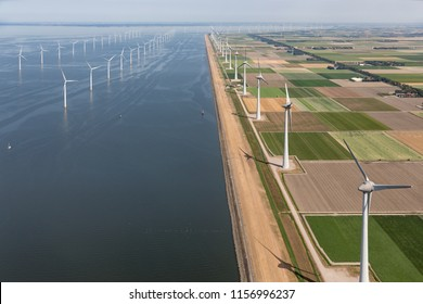 Aerial view Dutch agricultural landscape with big offshore wind turbines along the coast
