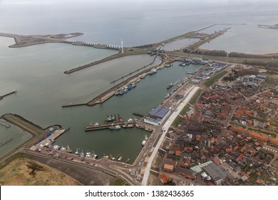 Aerial view Dutch harbor Den Oever with afsluitdijk, seperation between fresh water lake IJsselmeer and salt Wadden Sea