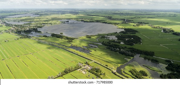 Aerial view of Dutch landscape. A nature reserve area at the Niewkoopse Plassen (Holland). Green fields, meadows, lakes and a crystal clear sky with cumulus clouds and cloud shadows on the ground.