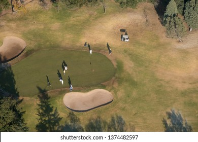 Aerial view of early morning golfers on green