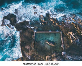 Aerial view early morning light with ocean waves flowing over rocks around North Curl Curl ocean rock pool