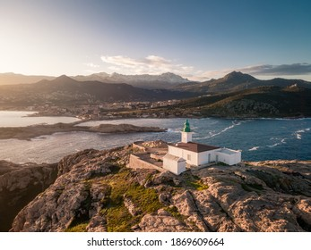 Aerial view of early morning sun on the lighthouse at La Pietra in Ile Rousse in the Balagne region of Corsica with snow capped mountains in the distance