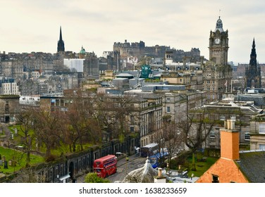 Aerial view of Edinburgh city skyline with red double decker bus in foreground and Edinburgh Castle in distance. Edinburgh Scotland UK. FEBRUARY 2020