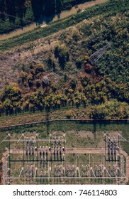 Aerial view of electricity power substation plant and pylons in the field, top view of industrial infrastructure from drone pov.