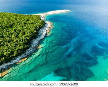 Aerial view of Emplisi Beach, picturesque stony beach in a secluded bay, with clear waters popular for snorkelling. Small pebble beach near Fiscardo town of Kefalonia, Ionian islands, Greece.