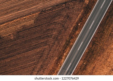 Aerial view of empty road through countryside on a sunny autumn day from drone pov
