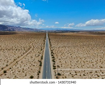 Aerial view of endless desert straight road next Joshua Tree Park. USA. Long straight tarmac road heading into the desert to the direction of Arizona.