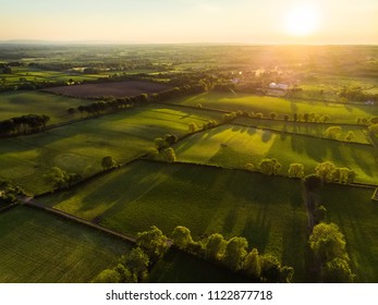 Aerial view of endless lush pastures and farmlands of Ireland. Beautiful Irish countryside with emerald green fields and meadows. Rural landscape on sunset.