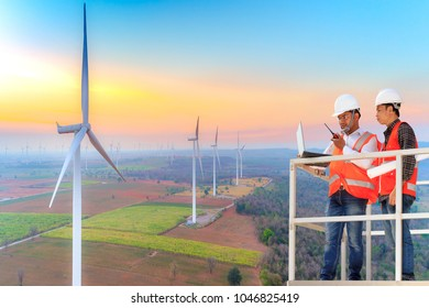 Aerial view of engineers and technician during working for checking and control working at wind turbine power generator station in beautiful sunrise
