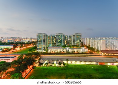 Aerial view of Eunos HDB next to MRT station in Singapore at twilight. Colorful city lights, electric train, car headlights in traffic. Neighborhood faculties car park and green garden at the center.