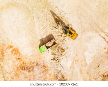 Aerial view of excavator loading dump truck with raw kaolin in kaolin open pit mine for ceramic tiles production. Industrial area from above. Industrial mining background texture concept.