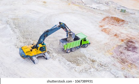Aerial view of excavator loading dump truck with raw kaolin in kaolin quarry for ceramic tiles production. Industrial area from above. Kaznejov, Czech republic, European union.
