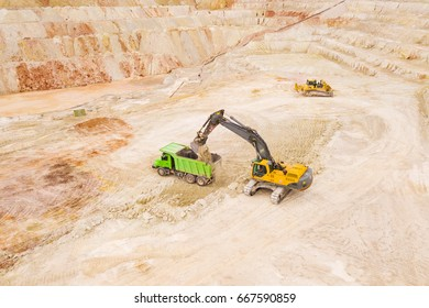 Aerial view of excavator loading dump truck with raw kaolin in kaolin open pit mine for ceramic tiles production. Industrial area from above. Kaznejov, Czech republic, European union.