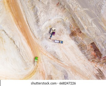 Aerial view of excavator loading dump truck with raw kaolin in kaolin open pit mine for ceramic tiles production. Industrial area from above.