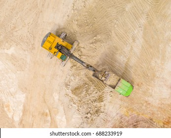 Aerial view of excavator loading dump truck with raw kaolin in kaolin open pit mine for ceramic tiles production. Industrial area from drone view. Background texture concept.