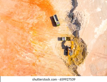 Aerial view of a excavator loading a truck in open cast mine or on construction site. Heavy industry from above. Industrial background from drone.