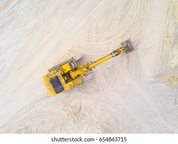 Aerial view of excavator working in kaolin quarry for ceramic tiles production. Industrial area from above. Chlumcany, Czech republic, European union.