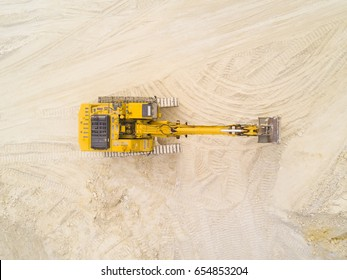 Aerial view of excavator working in quarry or construction site. Industrial top view background concept.