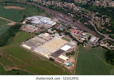 Aerial view of a factory or industrial area surrounded by green fields.