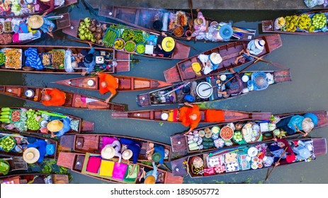 Aerial view famous floating market in Thailand, Damnoen Saduak floating market, Farmer go to sell organic products, fruits, vegetables and Thai cuisine, Tourists visiting by boat, Ratchaburi, Thailand