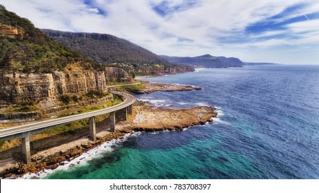 Aerial view of famous Sea Cliff Bridge on Grand Pacific drive in NSW, Australia. Scenic highway on the edge of sandstone cliff over tiding surfing waves of open Pacific ocean on a sunny day.