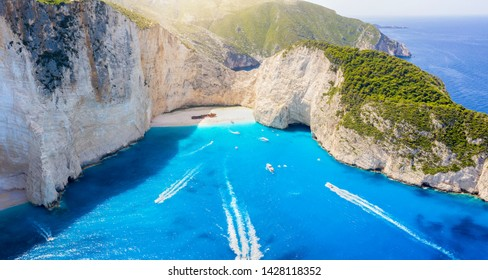 Aerial view of the famous shipwreck beach of Zakynthos island, Greece, with turquoise blue waters and excursion boat traffic