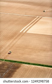 An aerial view of farm machinery planting potatoes in the fertile farm fields of Idaho.