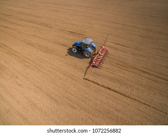 aerial view - Farmer with a tractor on the agricultural field sowing.  tractors working on the agricultural field in spring