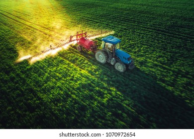 Aerial view of farming tractor plowing and spraying on field with motion blur.