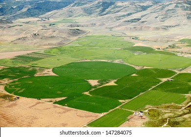 An aerial view of farmland and crop circles created by center pivot sprinkler systems