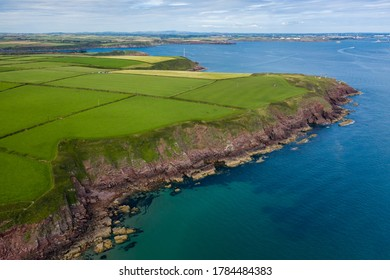 Aerial view of farms and fields on clifftops next to the ocean (Milford Haven, Wales, UK)